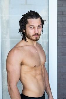 Portrait d'un bel homme sexy au repos à la piscine. concept de vacances d'été.
