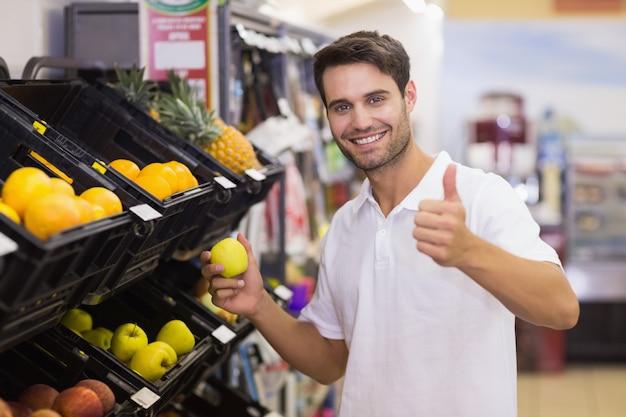 Portrait d'un bel homme souriant, acheter un fruit avec le pouce vers le haut