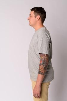 Portrait de bel homme avec des tatouages d'armes contre le mur blanc