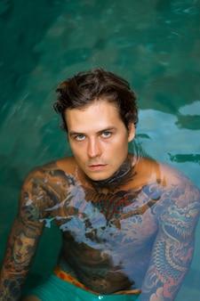 Portrait d'un bel homme tatoué à la piscine