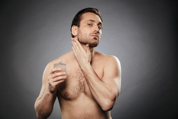 Portrait d'un bel homme torse nu à l'aide d'une lotion après-rasage