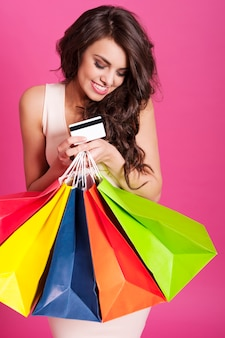 Portrait de belle accro du shopping sur rose
