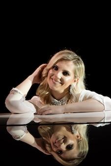 Portrait d'une belle actrice près d'un piano blanc.