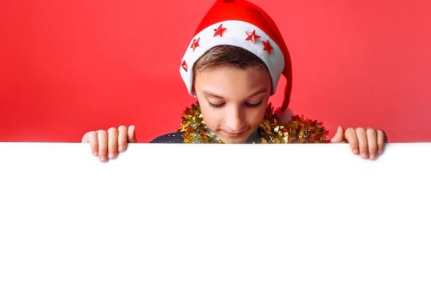 Portrait d'une belle adolescente au chapeau du père noël et avec des guirlandes sur son cou tenant un tableau blanc