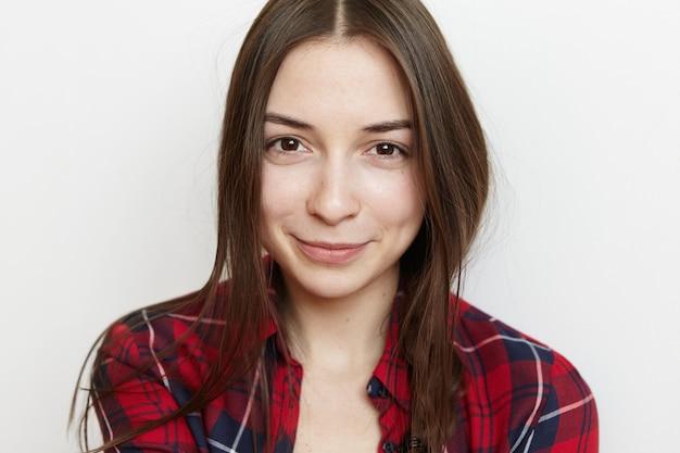 Portrait de la belle adolescente aux cheveux en désordre et joli sourire portant chemise à carreaux rouge