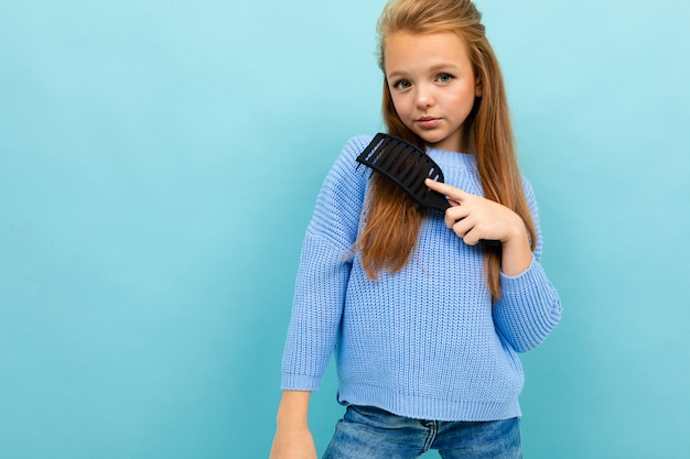 Portrait d'une belle adolescente aux cheveux longs et massage en peigne sur fond bleu