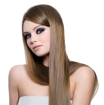 Portrait de la belle adolescente aux longs cheveux raides et maquillage des yeux noirs - fond blanc