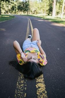 Portrait d'une belle adolescente couchée sur la route