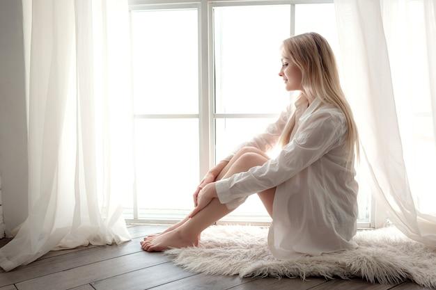 Portrait de belle adorable fille rêveuse gracieuse attrayante en lingerie chemise blanche profitant de la rêverie sur des draps en lin dans une chambre lumineuse blanche