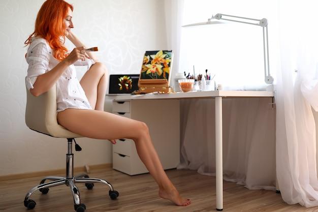 Portrait de la belle artiste féminine talentueuse assise sur une chaise et créant une image de fleur. femme aux cheveux rouges portant une chemise à la maison. concept d'art et de créativité