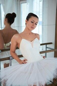 Portrait de la belle ballerine en tutu s'appuyant sur la barre et regardant vers le bas.