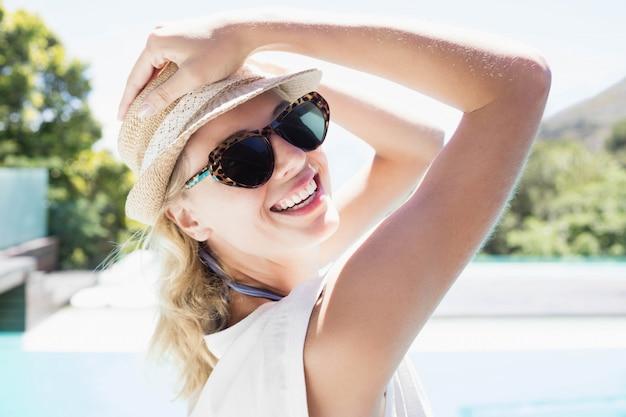 Portrait de belle blonde avec chapeau et lunettes de soleil