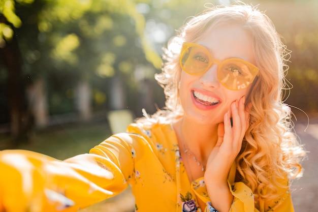 Portrait de la belle blonde élégante femme souriante en chemisier jaune portant des lunettes de soleil faisant selfie photo