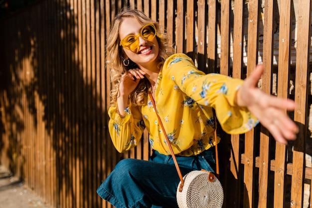 Portrait de belle blonde émotionnelle en riant élégante femme souriante en chemisier jaune portant des lunettes de soleil, sac à main en paille de style bali