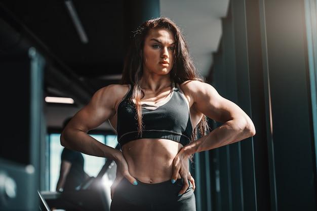 Portrait de la belle bodybuilder femme de race blanche posant avec les mains sur les hanches dans la salle de gym. la motivation est en vous.