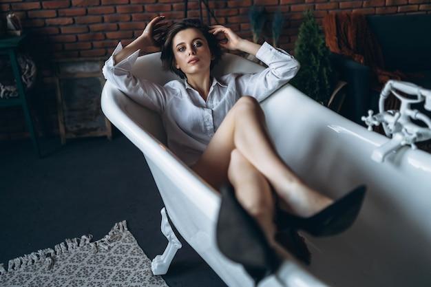 Portrait d'une belle brune couchée dans une salle de bain vide tenant les jambes