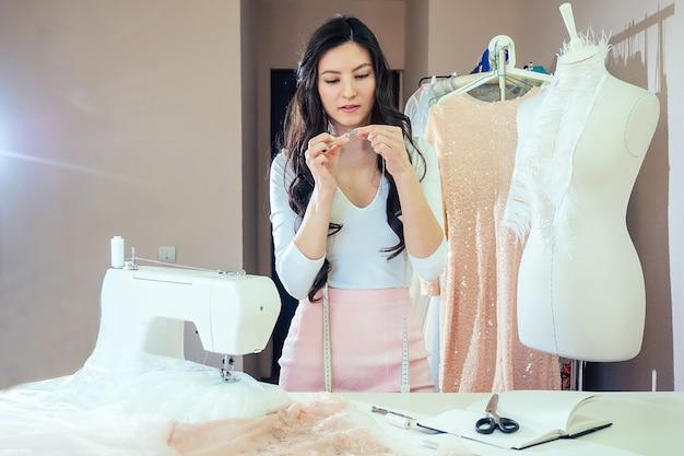 Portrait d'une belle couturière brune aux cheveux longs travaillant avec une machine à coudre. tailleur crée une collection de tenues . jeune femme créateur de mode coud des vêtements cousus à l'aiguille