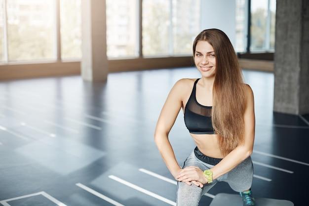 Portrait de belle dame adulte en forme qui s'étend ses jambes tôt le matin dans une salle de sport vide.