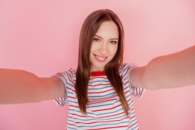 Portrait de belle dame assez positive prendre selfie sourire blanc brillant sur fond rose