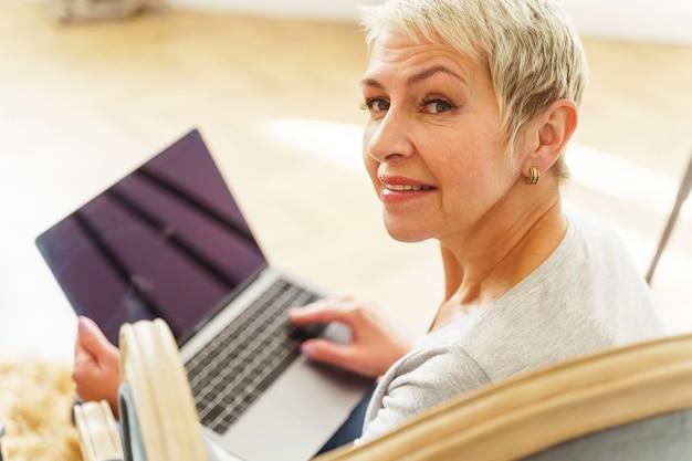 Portrait d'une belle dame caucasienne senior heureuse avec son ordinateur portable souriant