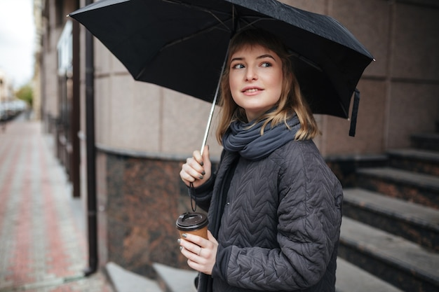 Portrait de belle dame debout sur la rue avec un parapluie noir à la main et rêveusement à côté