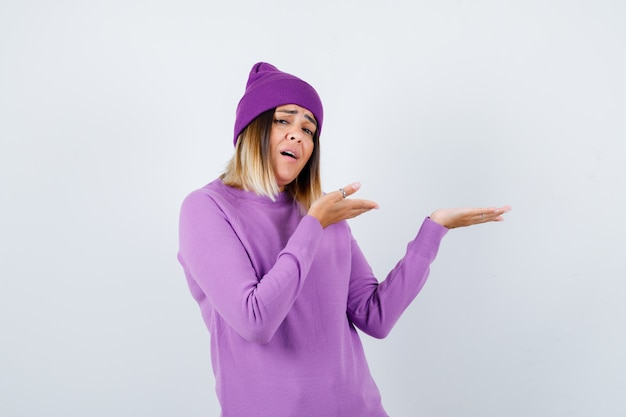 Portrait d'une belle dame faisant semblant de montrer quelque chose en pull, bonnet et regardant la vue de face troublée