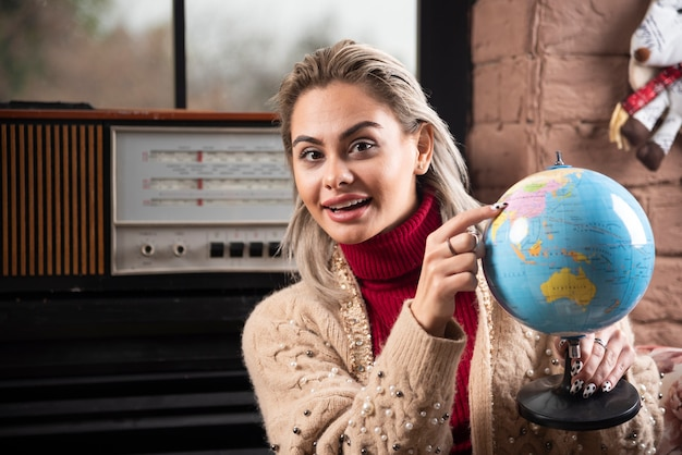Portrait de belle dame pointant sur un globe terrestre