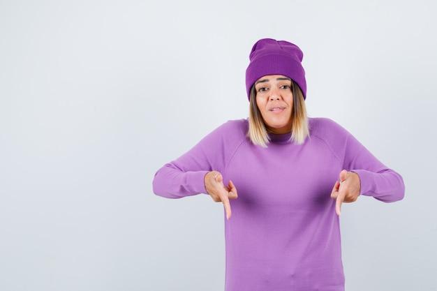 Portrait d'une belle dame pointant vers le bas en pull, bonnet et à la vue de face confiante