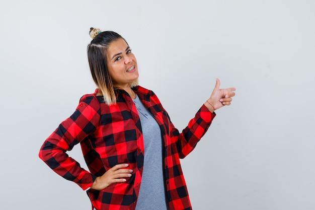 Portrait d'une belle dame pointant vers la droite, tenant la main sur la taille dans des vêtements décontractés et regardant la vue de face confiante