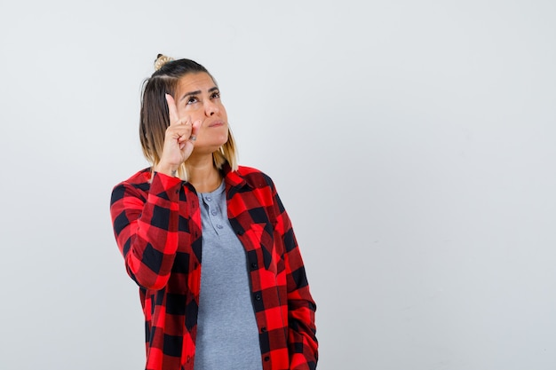 Portrait d'une belle dame pointant vers le haut, regardant vers le haut dans des vêtements décontractés et regardant la vue de face confiante