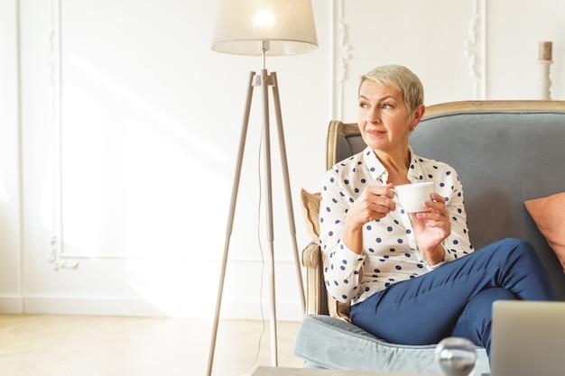Portrait d'une belle dame avec une tasse de thé assise en tailleur sur un canapé