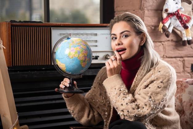 Portrait de belle dame tenant un globe terrestre
