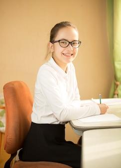 Portrait d'une belle écolière portant des lunettes posant derrière un bureau tout en faisant ses devoirs