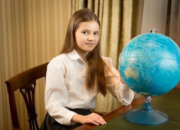 Portrait de belle écolière posant au cabinet avec globe terrestre