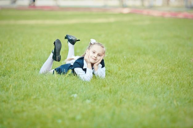 Portrait d'une belle écolière avec une queue de cochon et un arc blanc couché sur l'herbe verte te dans le parc