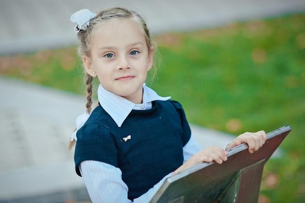 Portrait d'une belle écolière avec une queue de cochon et un arc blanc