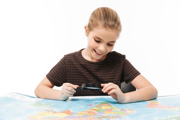 Portrait d'une belle écolière regardant la carte du monde à travers une loupe tout en étudiant la géographie à l'école isolée sur un mur blanc