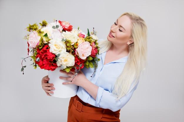 Portrait de belle et élégante femme blonde taille plus tenant une boîte avec des fleurs d'été sur fond gris