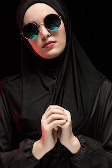 Portrait de la belle élégante jeune femme musulmane portant le hijab noir et des lunettes de soleil comme concept de mode orientale moderne sur fond noir