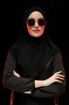 Portrait de la belle élégante jeune femme musulmane portant le hijab noir et des lunettes de soleil comme concept de mode orientale moderne posant