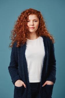 Portrait de belle étudiante au gingembre avec des cheveux ondulés et des taches de rousseur se tenant la main dans les poches, regardant avec un regard satisfait. plan vertical.
