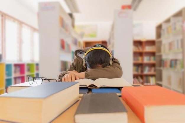 Portrait de belle étudiante brune fatiguée, assise parmi les livres