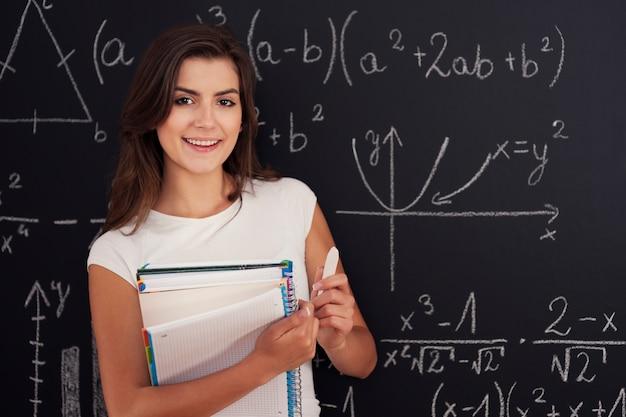 Portrait de la belle étudiante avec cahier à spirale et craie