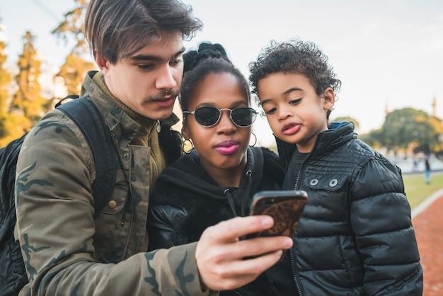 Portrait de belle famille ethnique métisse s'amuser, se détendre et utiliser un téléphone portable dans le parc à l'extérieur.