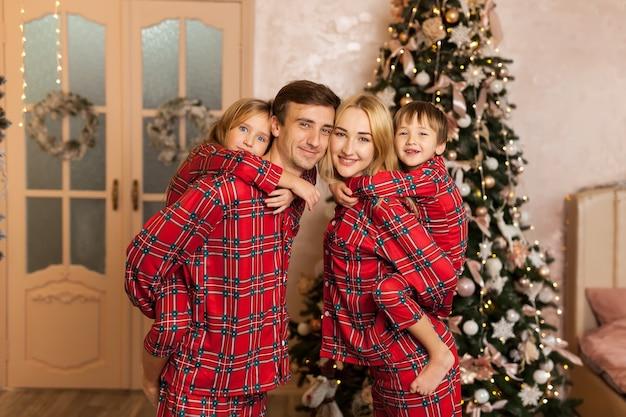 Portrait d'une belle famille mignonne en pyjama rouge festif