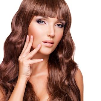Portrait d'une belle femme adulte avec de longs poils rouges avec les doigts au visage - isolé sur blanc.