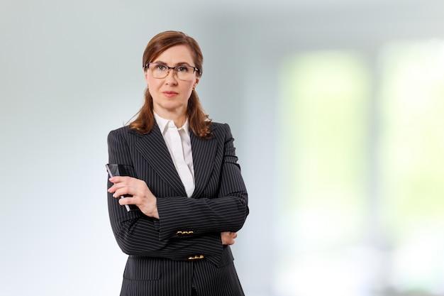 Portrait d'une belle femme d'affaires 50 ans avec téléphone portable au bureau.