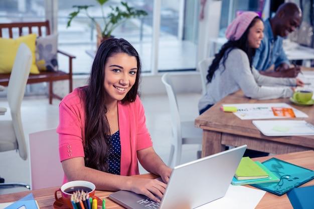 Portrait de belle femme d'affaires à l'aide d'un ordinateur portable tout en travaillant avec des collègues de bureau créatif