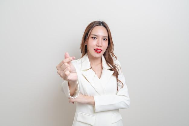 Portrait belle femme d'affaires asiatique avec signe de la main mini coeur