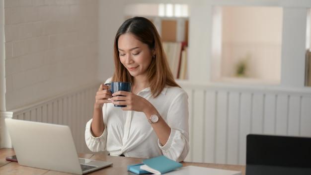 Portrait de la belle femme d'affaires asiatique travaillant sur son projet et buvant un café